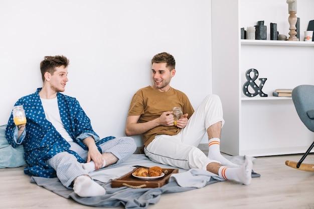 Hübsche glückliche männer, die das sitzen auf boden frühstücken Kostenlose Fotos