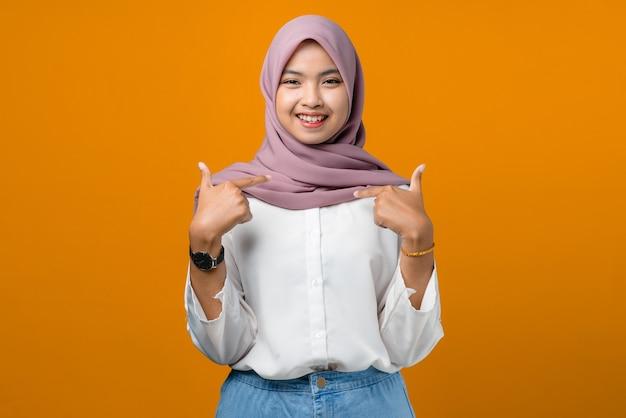 Hübsche junge asiatische frau, die sich auf gelb glücklich fühlt Premium Fotos