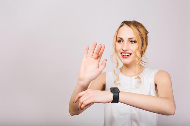 Hübsche junge blonde frau, die mit ihren händen winkt und mit einem lächeln isoliert posiert. charmantes mädchen mit lockigem haar, das stilvolles trägershirt trägt, das lacht und neue schwarze armbanduhr zeigt Kostenlose Fotos