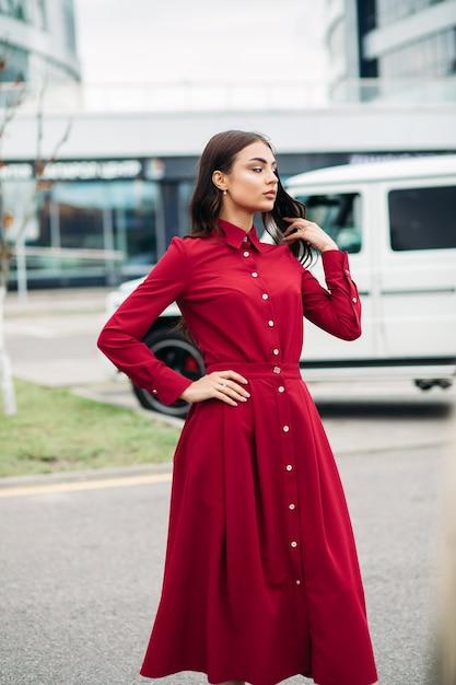 Hübsche junge dame, die rotes kleid trägt, während auf der straße mit auto und gebäude auf dem hintergrund aufwirft. stadtlebensstil Kostenlose Fotos
