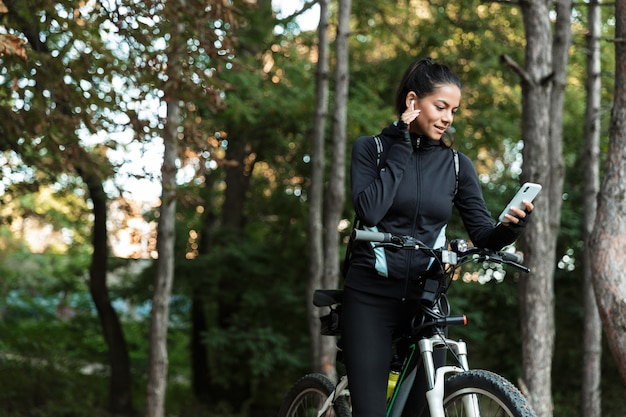 Hübsche junge fitnessfrau, die auf einem fahrrad am park reitet, musik mit kopfhörern hört, handy hält Premium Fotos