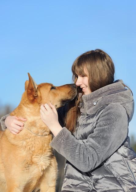 Hübsche junge frau des porträts, ihren hund des guten freunds küssend Premium Fotos