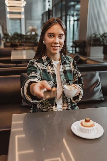 Hübsche junge frau, die eine kaffeepause genießt Kostenlose Fotos
