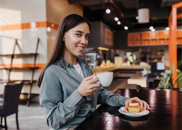 Hübsche junge frau, die eine kaffeepause genießt Premium Fotos