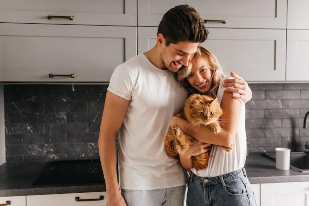 Hübsche junge frau, die katze während des familienporträts hält. netter brünetter mann, der seine frau umarmt. Kostenlose Fotos