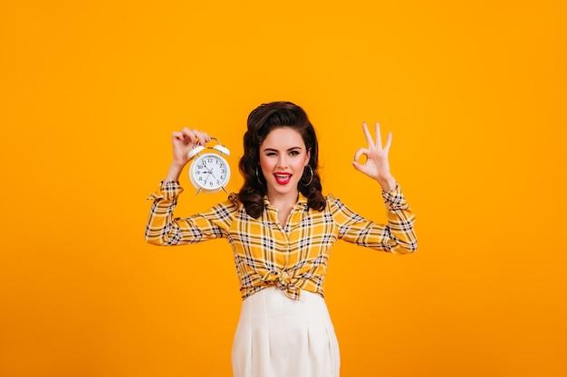 Hübsche junge frau, die mit uhr und in ordnung zeichen aufwirft. lächelndes pinup-mädchen im karierten hemd, das auf gelbem hintergrund steht. Kostenlose Fotos