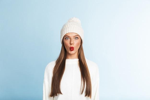 Hübsche junge frau, die pullover und hut stehend trägt Premium Fotos
