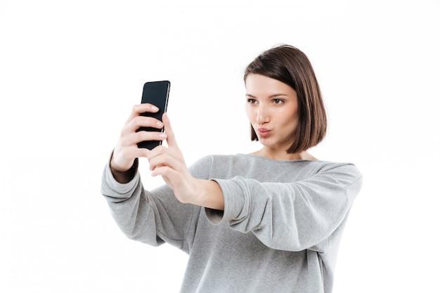 Hübsche junge frau, die selfie auf handy nimmt Kostenlose Fotos