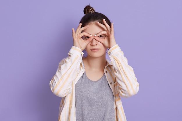 Hübsche junge frau mit verärgertem gesicht, das finger nahe augen wie brille hält Kostenlose Fotos