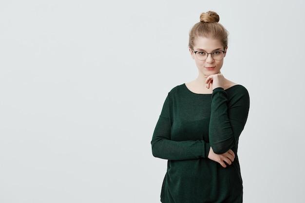 Hübsche junge frau sieht mit anziehungskraft aus, wenn ihr blondes haar mit einer großen brille und einem grünen, losen pullover, der die hand unter ihrem kinn hält, zu einem knoten zusammengebunden ist, pläne erstellt und über etwas nachdenkt Kostenlose Fotos