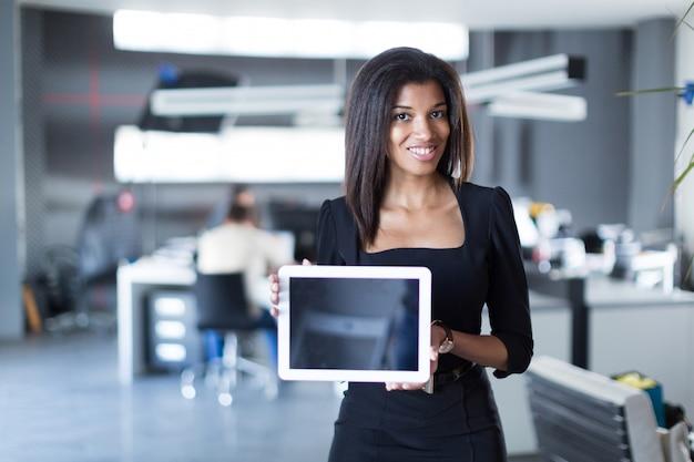 Hübsche, junge geschäftsdame in der schwarzen starken reihengrifftablette Premium Fotos