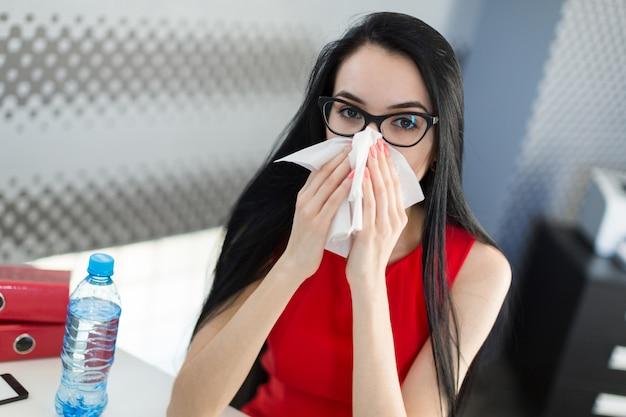 Hübsche, junge geschäftsfrau in rotem kleid und brille sitzen am tisch und arbeiten Premium Fotos