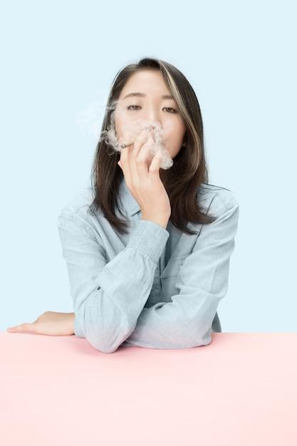 Hübsche junge koreanische frauen, die zigarre rauchen, während sie am tisch im studio sitzen. Kostenlose Fotos