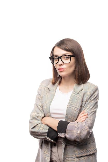Hübsche junge lehrerin in abendgarderobe, die dich mit strengem ausdruck ansieht und die arme vor der brust verschränkt Premium Fotos