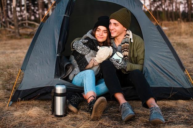 Hübsche junge leute mit einem zelt im freien Kostenlose Fotos