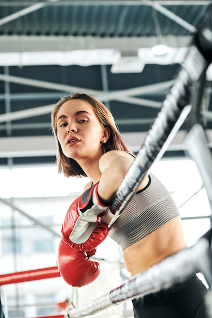 Hübsche junge selbstbewusste frau in aktivkleidung und boxhandschuhen, die an eisbahnstangen stehen, während sie pause zwischen den trainingseinheiten im fitnessstudio genießen Premium Fotos