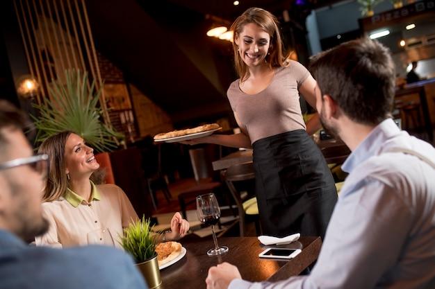 Hübsche kellnerin, die gruppe von freunden mit essen im restaurant dient Premium Fotos