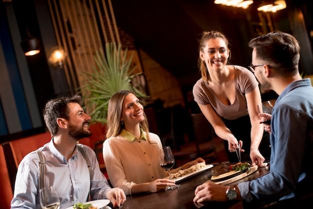 Hübsche kellnerin, die gruppe von freunden mit essen in der gastronomie dient Premium Fotos