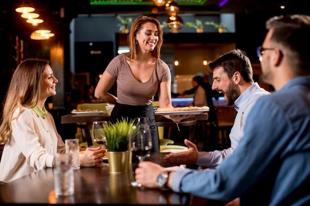 Hübsche kellnerin serviert gruppe von freunden mit essen im restaurant Premium Fotos