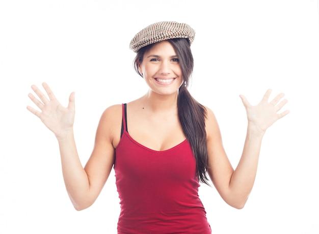 Hübsche lächelnde und nette brunettefrau mit französischer kappe und rotem trägershirt Premium Fotos