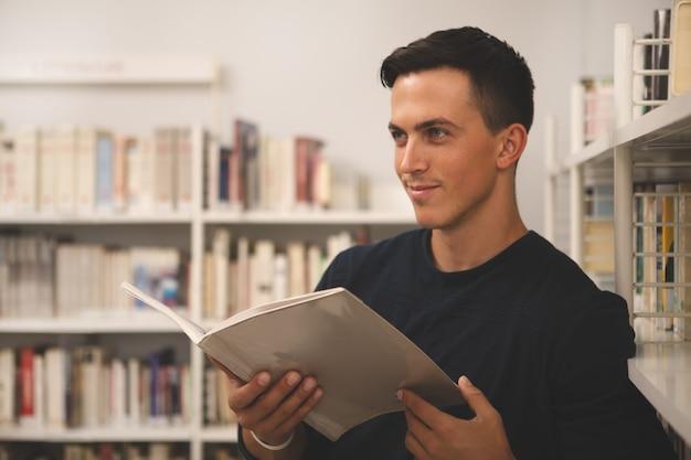 Hübsche lesung des jungen mannes an der bibliothek Premium Fotos