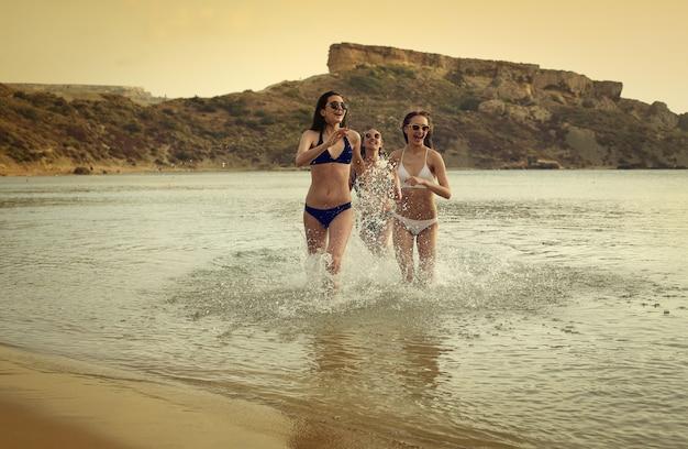 Hübsche mädchen, die in das meer laufen Premium Fotos