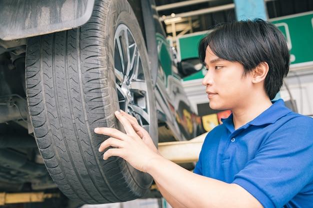 Hübsche mechaniker in uniform arbeiten im auto-service mit leichtmetallrad. Premium Fotos
