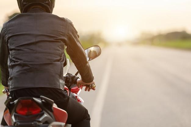 Hübsche motorradfahrer-abnutzungslederjacke, sturzhelm auf der straße halten Premium Fotos