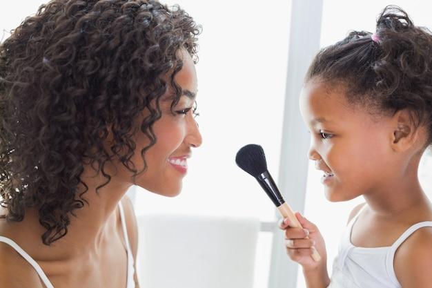 Hübsche mutter, die ihre tochter über make-up unterrichtet Premium Fotos