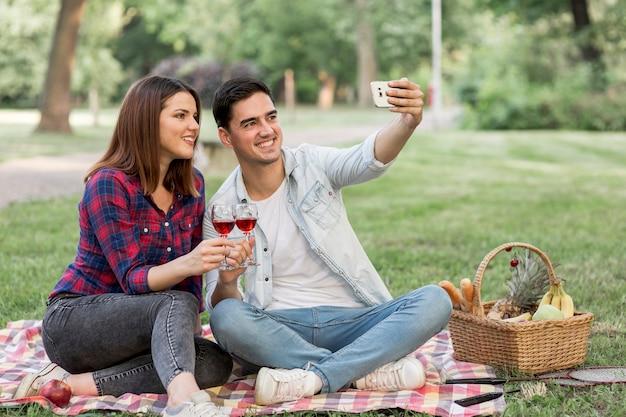 Hübsche paare, die ein selfie beim halten von weingläsern nehmen Kostenlose Fotos