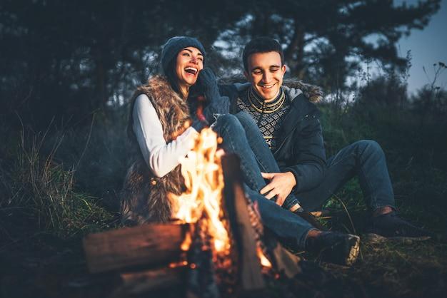 Hübsche paare, die nahe feuer im wald zur abendzeit sich entspannen Premium Fotos