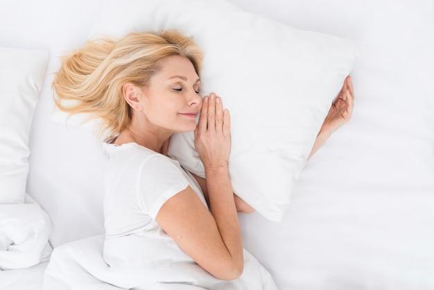 Hübsche reife frau der draufsicht, die ein schläfchen hält