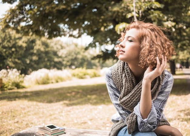 Hübsche rothaarigefrau, die auf bank im park sitzt Kostenlose Fotos