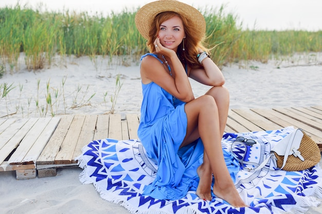 Hübsche schlanke frau mit langen roten haaren im strohhut, die erstaunliche urlaubszeit am strand verbringen. blaues kleid tragen. sitzen auf stilvollem cover. Kostenlose Fotos