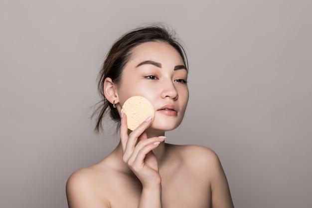 Hübsche schönheit junge asiatische frau, die ihr gesicht mit wattepad über weiß lokalisiert auf weißer wand reinigt. gesundes haut- und kosmetikkonzept. Kostenlose Fotos