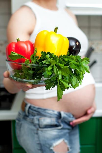 Hübsche schwangere frau, die eine platte mit gemüse und kräutern hält Premium Fotos