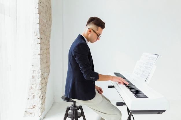 Hübsche übende klaviertastatur des jungen mannes Kostenlose Fotos