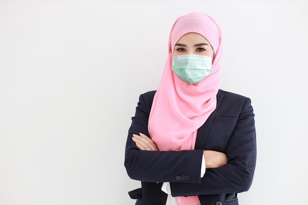 Hübsche und selbstbewusste muslimische junge asiatische frau, die blauen anzug mit medizinischer schützender gesichtsmaske trägt, um infektion von coronavirus im studio auf lokalisiertem weißem hintergrundporträt zu schützen Premium Fotos