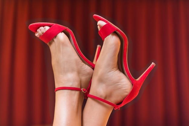 Hübsche weibliche füße in roten sandalen mit hohem absatz Premium Fotos
