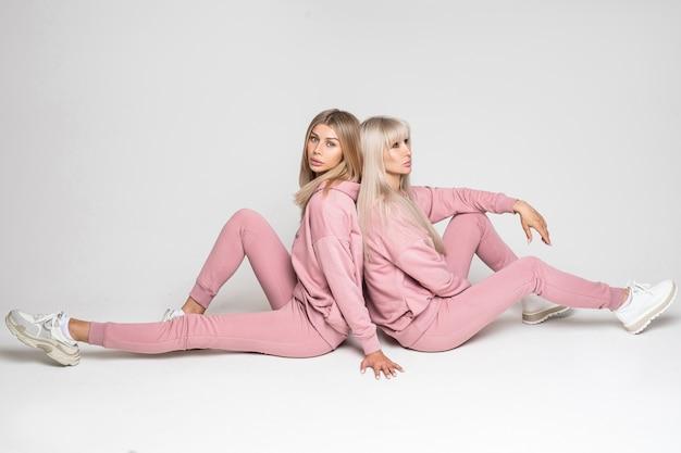 Hübsche zwei damen, die rücken an rücken sitzen und warme herbstkostüme zeigen, während sie auf grauem hintergrund posieren Premium Fotos