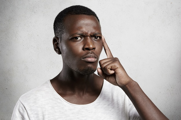 Hübscher afrikanischer mann mit misstrauen und zweifel, der gegen betonwand aufwirft. Kostenlose Fotos