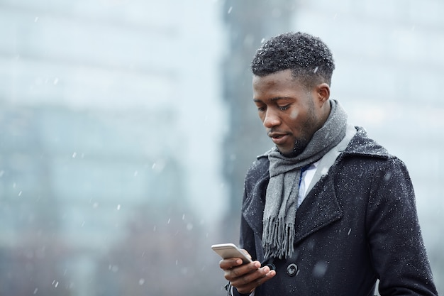 Hübscher afrikanischer mann mit smartphone im schnee Kostenlose Fotos