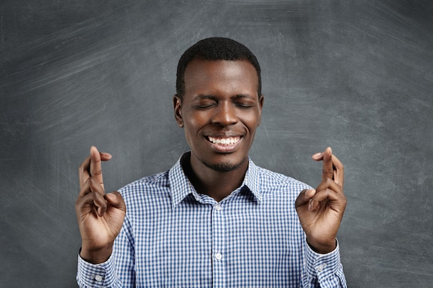 Hübscher afrikanischer student in kariertem hemd, der seine finger an beiden händen kreuzt und die augen geschlossen hält, wünsche macht, auf das beste hofft und um wunder betet und prüfungen mit hohen noten bestehen möchte Kostenlose Fotos