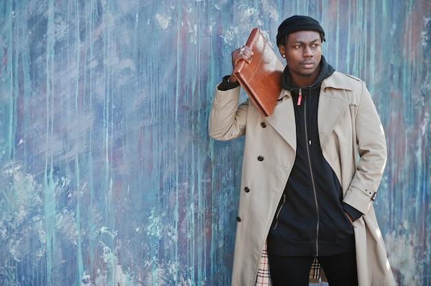 Hübscher afroamerikanermann, der draußen im schwarzen hut und im beigen mantel mit ordner in der hand aufwirft. Premium Fotos