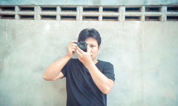 Hübscher asiatischer kerl, der foto mit kamera macht Premium Fotos