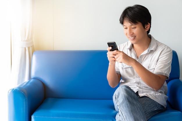 Hübscher asiatischer mann, der handy beim sitzen auf blauem sofa am morgen verwendet Premium Fotos