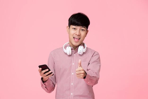 Hübscher asiatischer mann mit den kopfhörern und smartphone, die daumen aufgeben Premium Fotos
