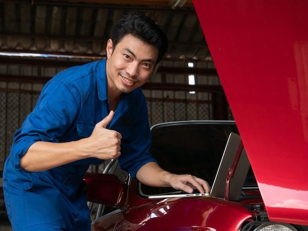 Hübscher asiatischer mechaniker, der laptop-computer verwendet, um einen automotor zu überprüfen und sich daumen an der reparaturgarage zu zeigen. Premium Fotos