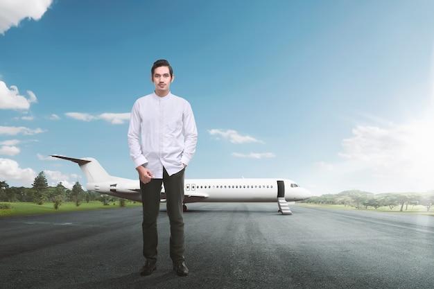 Hübscher asiatischer moslemischer mann, der mit flugzeug steht Premium Fotos