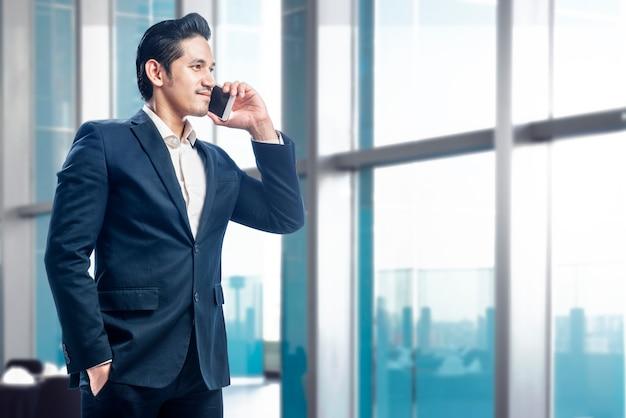 Hübscher asiatischer stehender geschäftsmann bei der unterhaltung auf dem mobiltelefon Premium Fotos